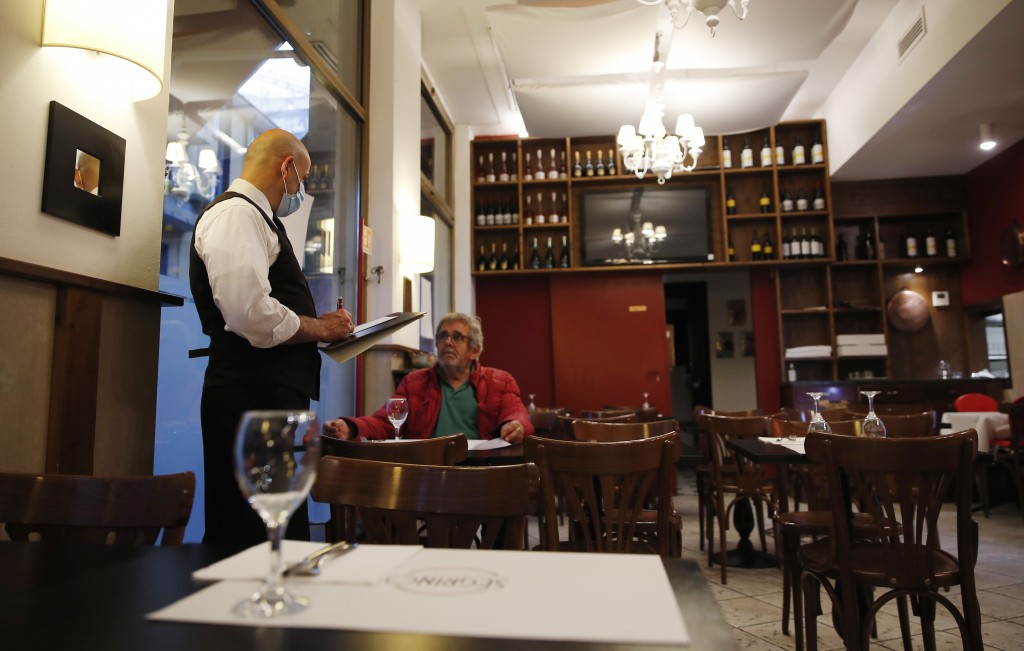"In this photo taken on Tuesday, May 19, 2020, a waiter reads the menu to a client at the ""La Rotonda di Segrino"" restaurant in Milan, Italy. Italy's r..."