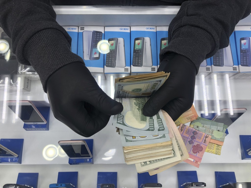 In this Tuesday, April 28, 2020, a cellphone owner shop wears gloves as he counts money on his shop, in Beirut, Lebanon. Public officials and health e...