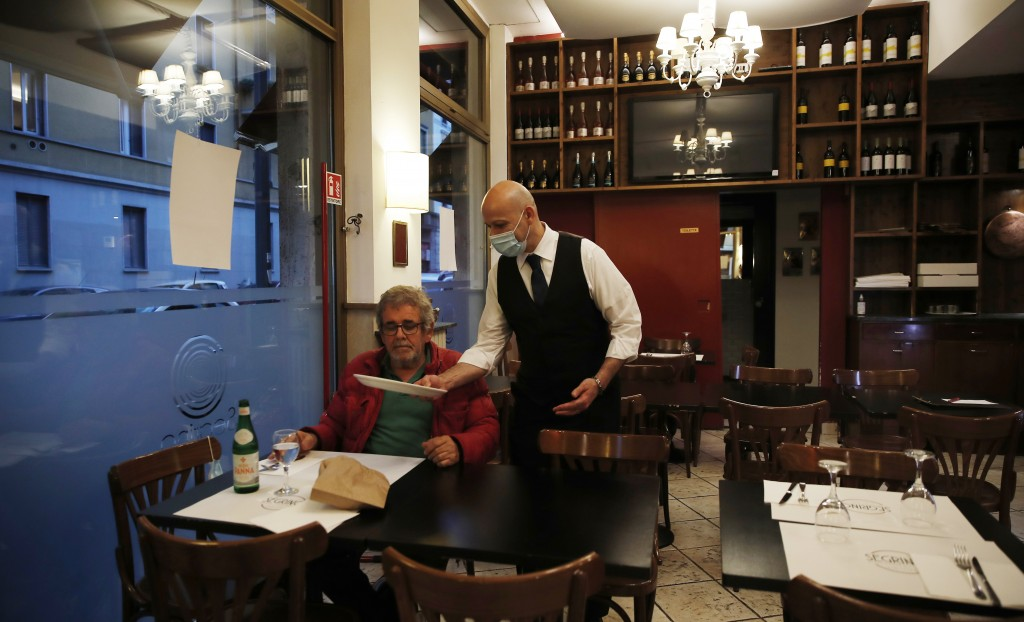 "In this photo taken on Tuesday, May 19, 2020, a waiter tends to a customer at the ""La Rotonda di Segrino"" restaurant in Milan, Italy. Italy's restaura..."