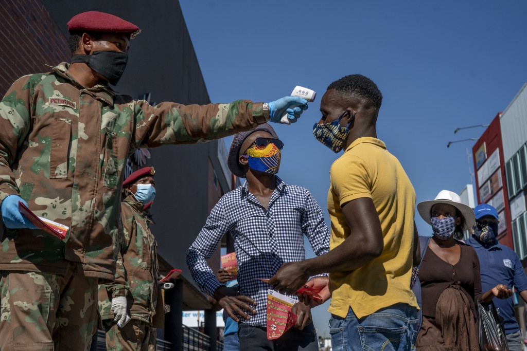 South African National Defense Forces check people's temperature near the Pan Africa taxi rank in Johannesburg's Alexandra township, Wednesday May 20,...