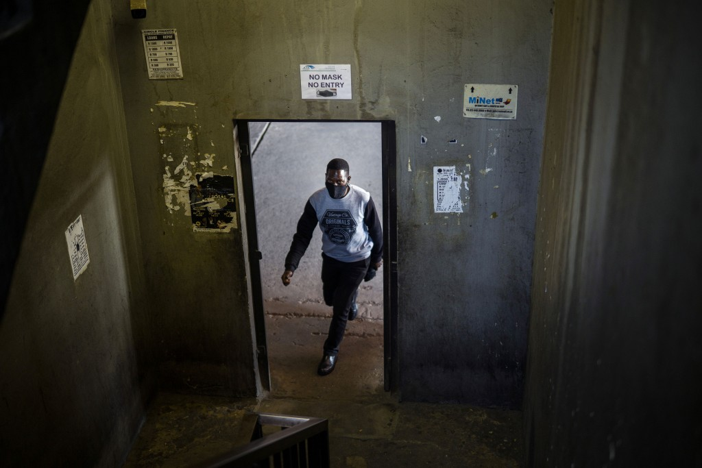 A man walks in the Pan Africa taxi rank in Johannesburg's Alexandra township Wednesday May 20, 2020, where a massive sanitization effort as well as Co...
