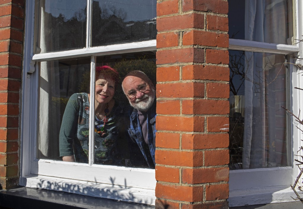 Bob and Sue Parsons look out from their window in Berkhamsted, England, Thursday, March 26, 2020. Bob and his wife Sue have lived there for 40 years. ...