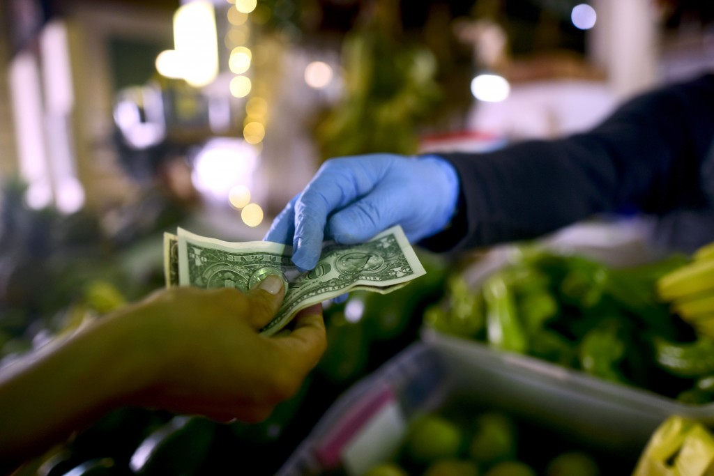 FILE - In this March 19, 2020, file photo, Jorge Otero, owner of a fruit and vegetables stand, wears gloves as he exchanges cash with a customer, duri...
