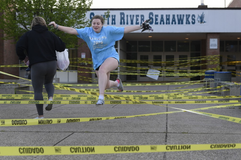 South River High School Class of 2020 senior Aly Yates of Edgewater, Md., jumps over caution tape outside the South River High School in Edgewater, Md...