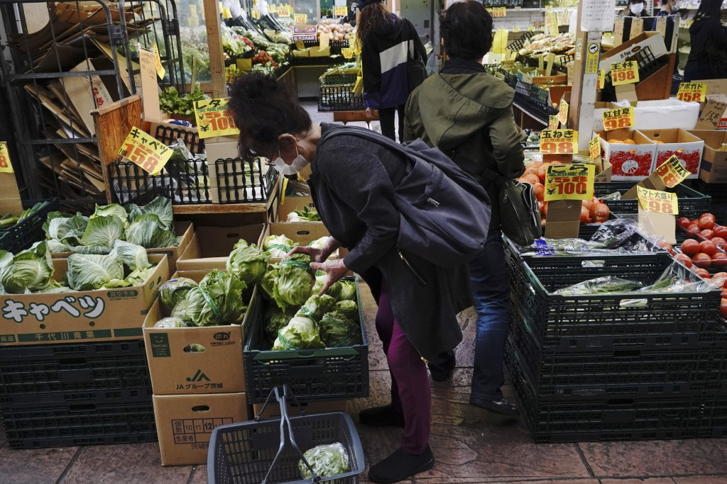 A woman wearing a face mask to help curb the spread of the coronavirus buys vegetable at a shop Wednesday, May 20, 2020, in Tokyo. Japan's prime minis...