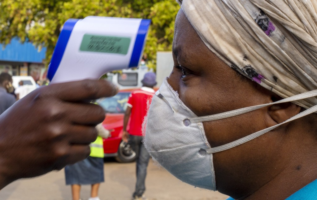 A woman wearing face masks to protect against coronavirus, has her temperature checked by a security personnel before entering a grocery shop at Tembi...