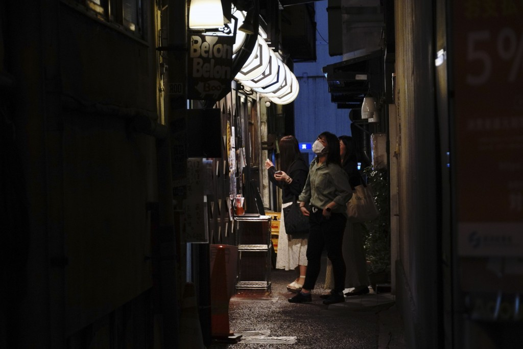 Women speak in front of a bar on an ally of bar streets in Tokyo Thursday, May 14, 2020. While Tokyo is still under a coronavirus state of emergency, ...
