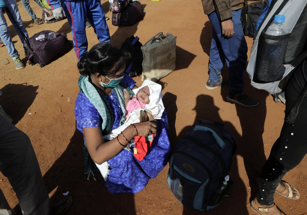 Baby Harsh Sharma, born during the lockdown in Mumbai is seen in his mother's arms as she lines up to board a bus  for their onward journey by train t...