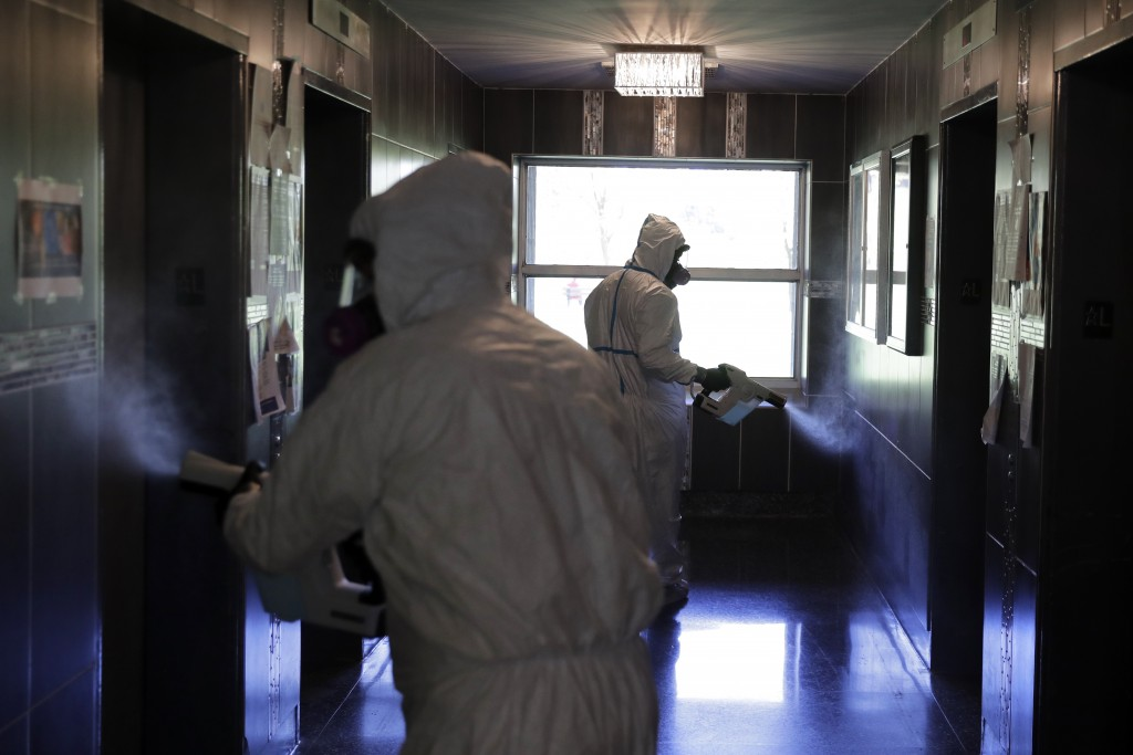 Environmental Specialist Anthony Olivieri, right, and Safety Director Tony Barzelatto disinfect a lobby of a building in Co-op City in the Bronx borou...