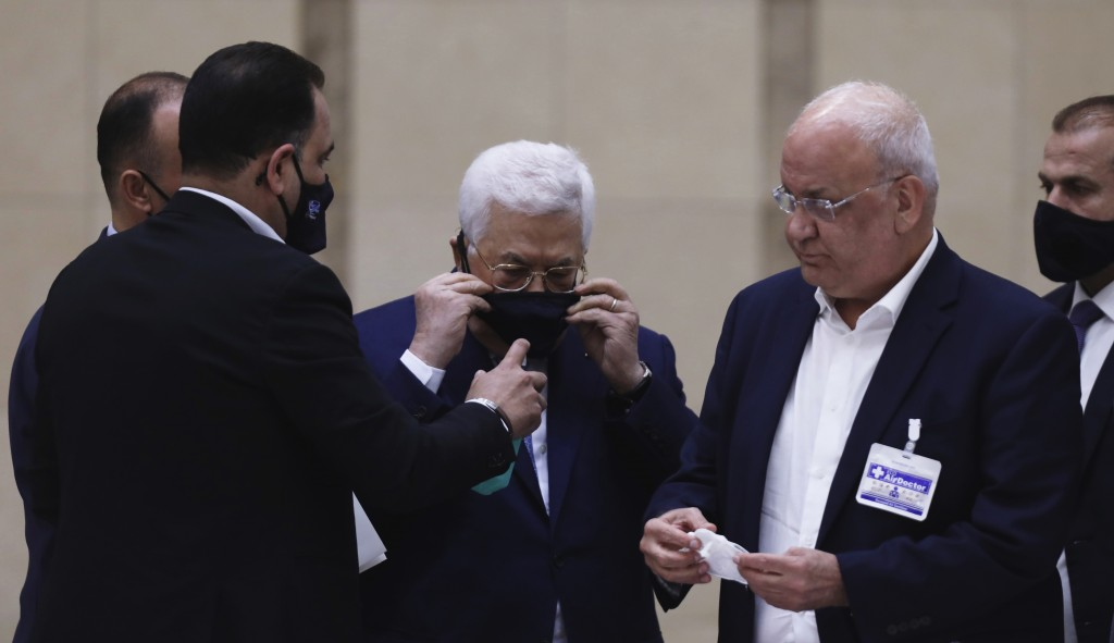Palestinian President Mahmoud Abbas puts on a face mask as he heads a leadership meeting at his headquarters in the West Bank city of Ramallah on Tues...