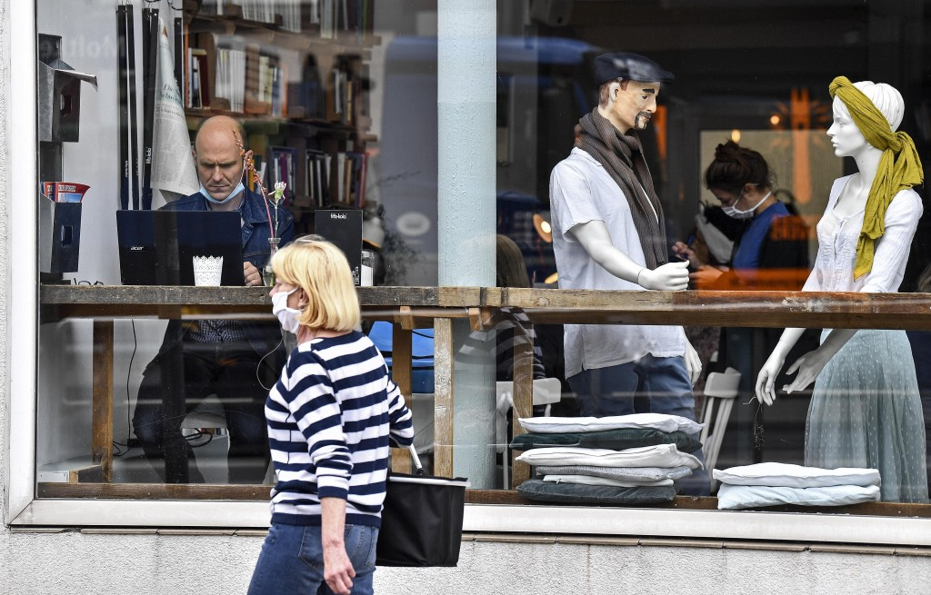 A customer sits with his laptop beside display mannequins at the Cafe Livres in Essen, Germany, Wednesday, May 20, 2020. The cafe set the dolls as pla...