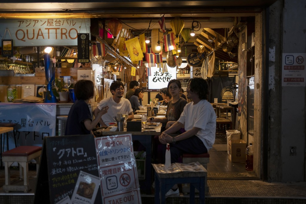 People gather for dinner and drinks at a restaurant in Tokyo  May 11, 2020. In this country driven by conformity and consensus, the pandemic is pittin...