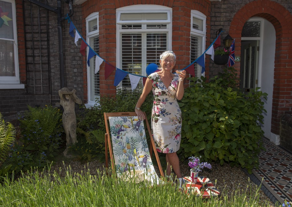 Jo Banks drinks a shandy in her front garden decorated with bunting and a Union Jack during Victory in Europe Day celebrations in Berkhamsted, England...
