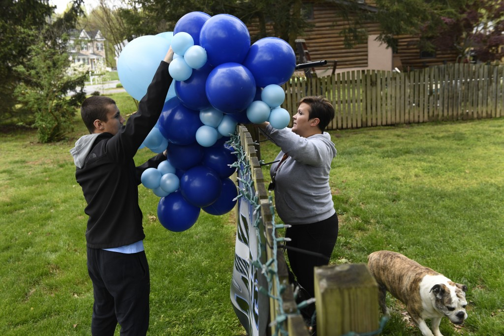 Lisa Sullivan, center, and her son Joey Hartge, left, install balloons along a fence at their Edgewater, Md., home Saturday, April 25, 2020, as their ...