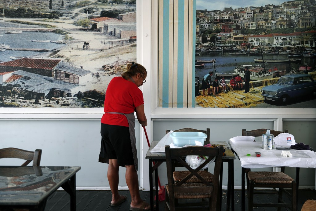 A worker cleans a fish restaurant ahead of its reopening in Piraeus, near Athens, Wednesday, May 20, 2020. Next Monday, bars, cafes and restaurants wi...