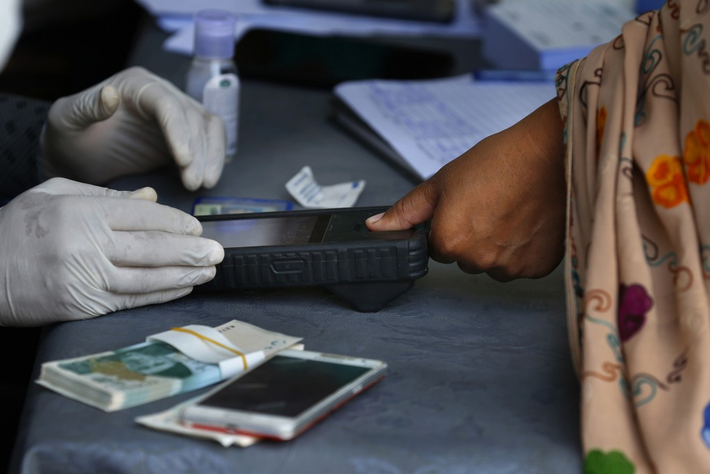 FILE - In this April 11, 2020, file photo, a woman scans her thumb for identification to receive cash under the governmental Ehsaas Emergency Cash Pro...