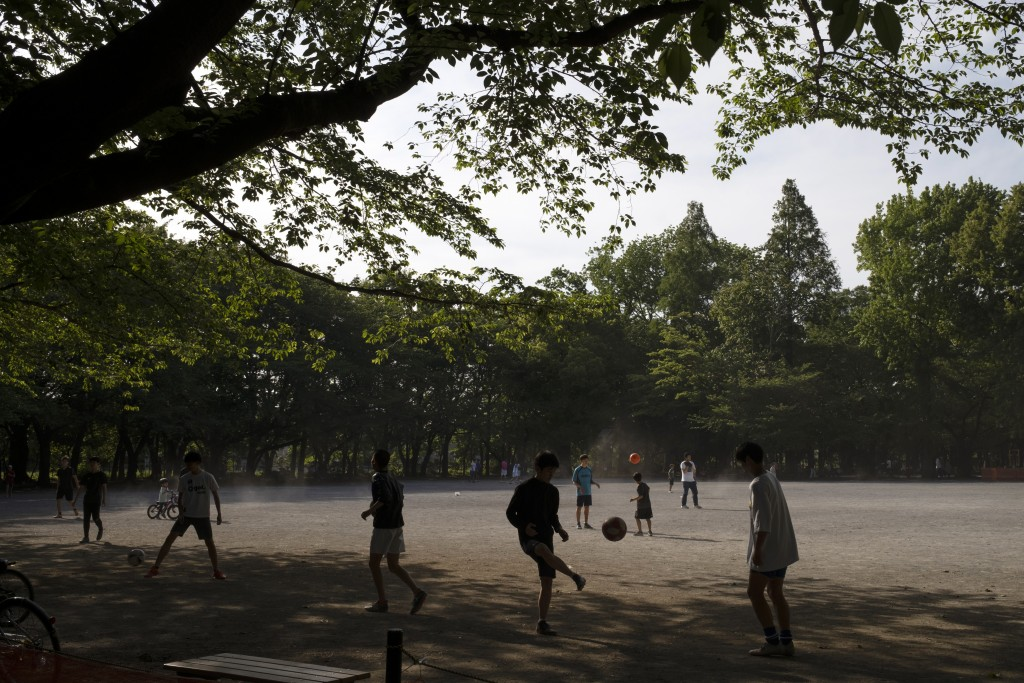 People play in a park in Tokyo Thursday, May 14, 2020. In this country driven by conformity and consensus, the pandemic is pitting those willing to fo...