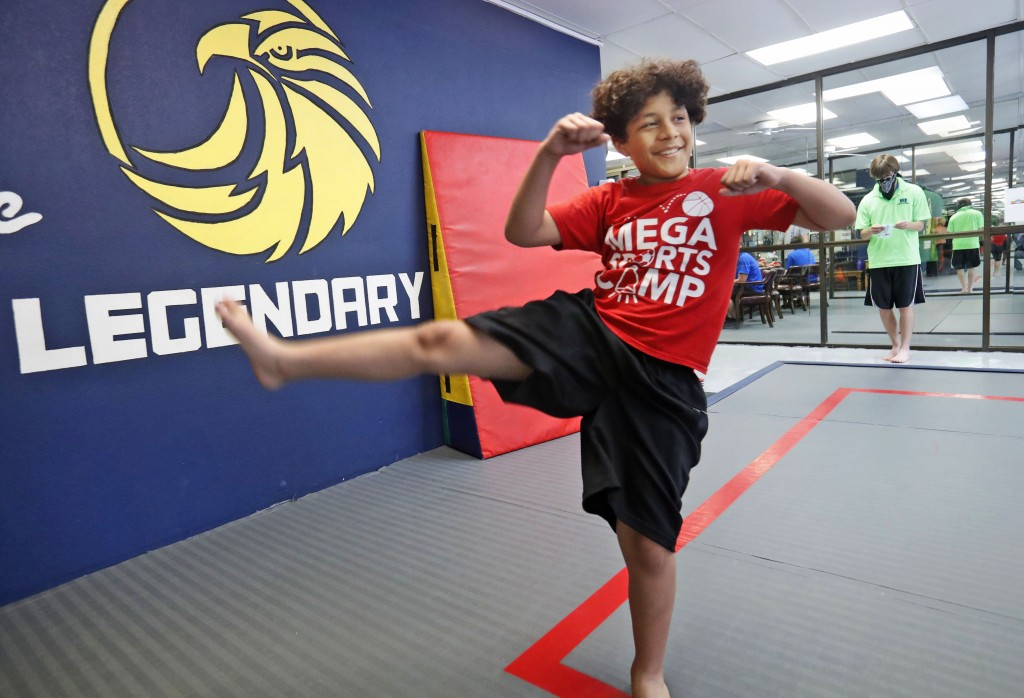 Ty Fenton, 11, smiles as he kicks during martial arts daycare summer camp at Legendary Blackbelt Academy in Richardson, Texas, Tuesday, May 19, 2020. ...