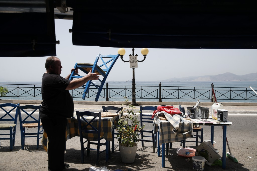 A worker places chairs at a fish restaurant ahead of its reopening in Piraeus, near Athens, Wednesday, May 20, 2020.Next Monday, bars, cafes and resta...