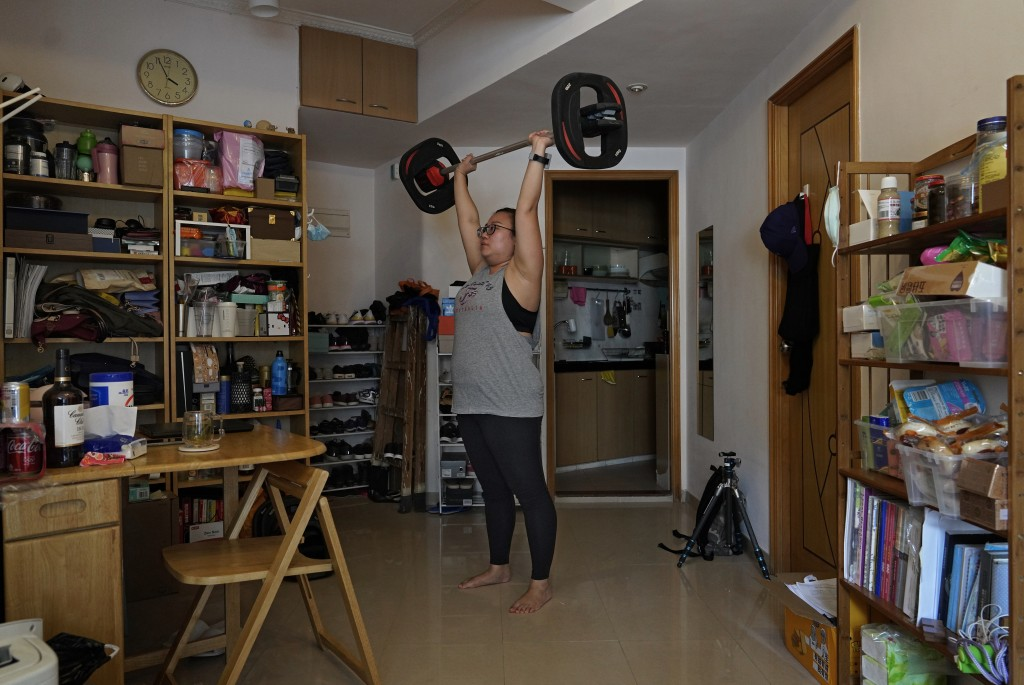 Associated Press reporter Zen Soo lifts weights at home while serving a two-week home quarantine in Hong Kong, April 17, 2020. (AP Photo/Vincent Yu)