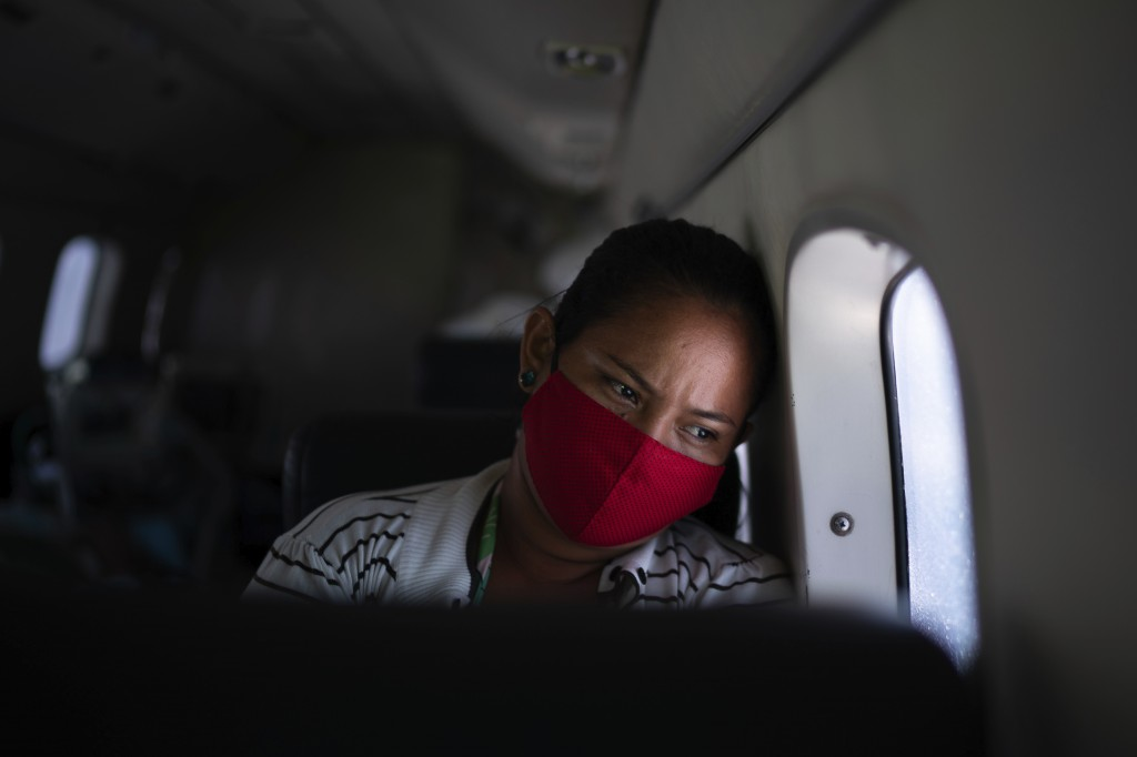 Telma Maria looks out of the window as a doctor monitors her 89-year-old father who is suffering from COVID-19 and is being airlifted from Santo Anton...