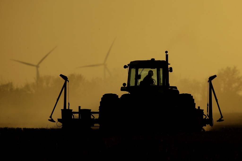 Dallas Koehn plants milo in his field as wind turbines rise in the distance, Tuesday, May 19, 2020, near Cimarron, Kan. President Donald Trump announc...