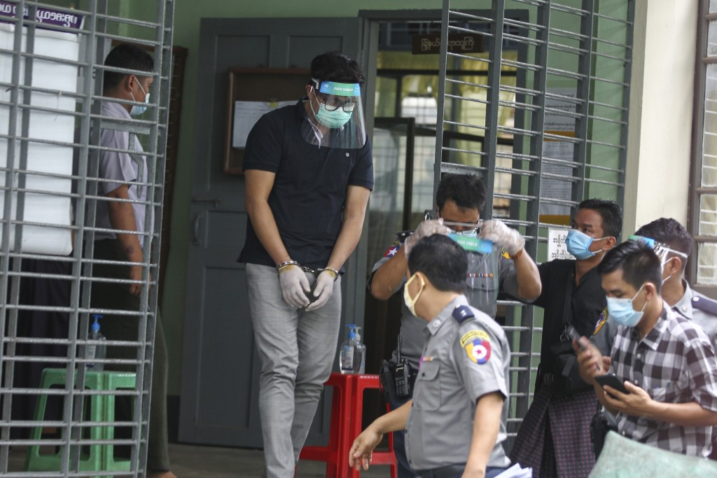 Canadian pastor David Lah cuffed wearing face shield and mask is escorted by police as he leaves from a township court after his first appearance Wedn...