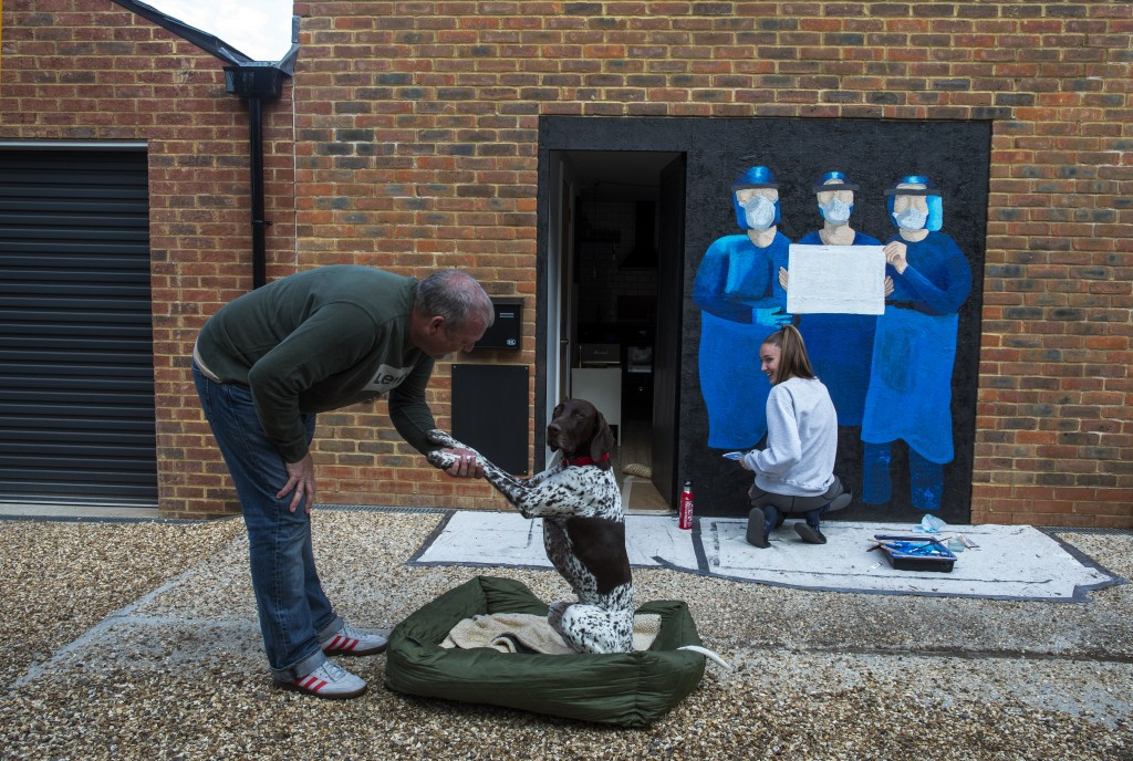 Meg Johnson-Jones, right, who is painting a mural to acknowledge workers in the National Health Service looks at Ivy shake her paw with her dad Mat Se...