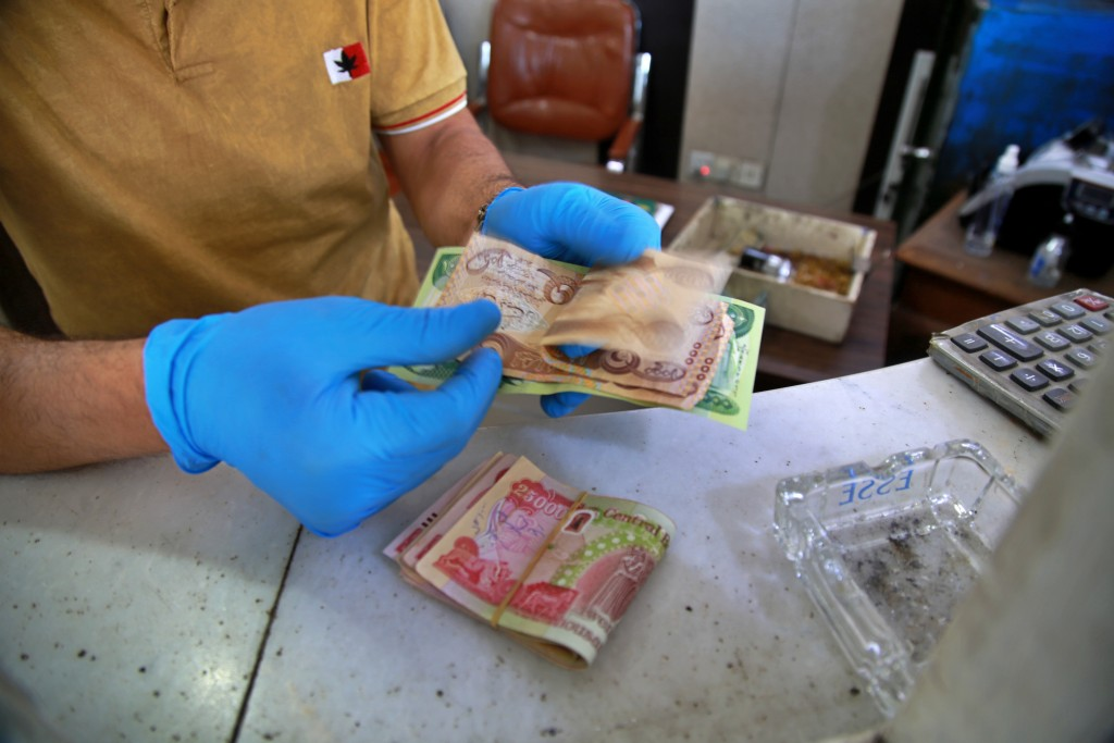 In this Sunday, May, 3, 2020, an Iraqi money changer counts banknotes in Baghdad, Iraq. The pandemic has also reawakened debate about the continued vi...