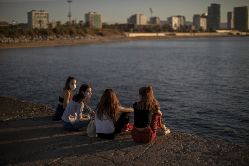 A group of women wearing face masks sit in front of sea in Barcelona, Spain, Wednesday, May 20, 2020. Barcelona permitted Wednesday for people to walk...