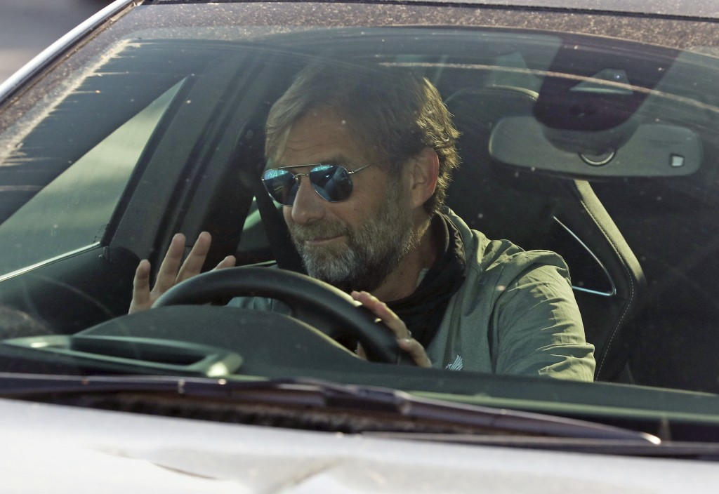 Liverpool soccer team manager Jurgen Klopp waves as he arrives at the club's Melwood training ground after the English Premier League announced player...
