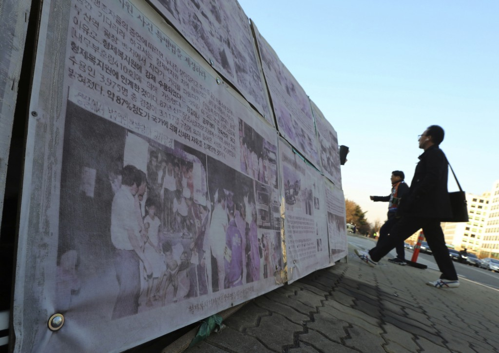 In this April 2, 2019, file photo, people walk past a photo of guards unloading children from a truck at the Brothers Home in Busan as it is displayed...
