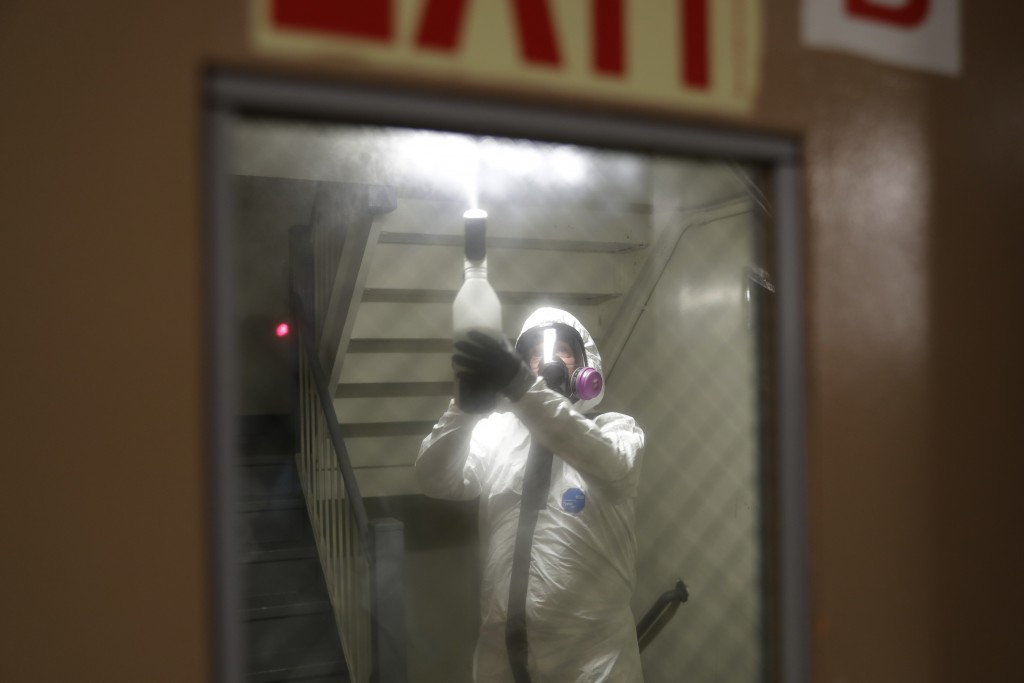 Safety Director Tony Barzelatto sprays disinfectant in a stairwell in Co-op City in the Bronx borough of New York, Wednesday, May 13, 2020. Regular cl...