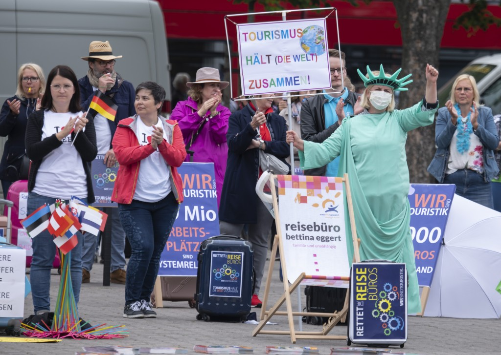 A woman dressed as New York's Statue of Liberty attends a demonstration of the tourism business at the cathedral square in Erfurt, Germany, Wednesday,...