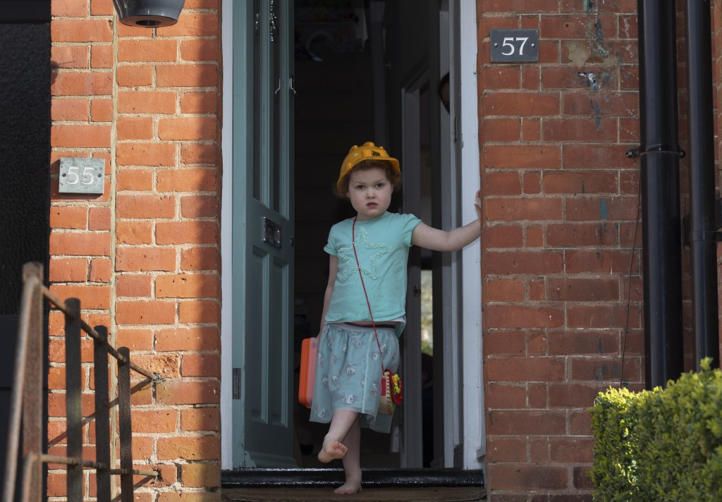 Chloe Kelly stands at her door dressed up and in a hard hat in Berkhamsted, England, Friday, April 3, 2020. Despite the lockdown Chloe and her sister ...