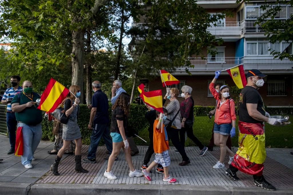 People holding Spanish flags protest against the Spanish government amid the lockdown to prevent the spread of coronavirus in Alcorcon, Spain, Wednesd...