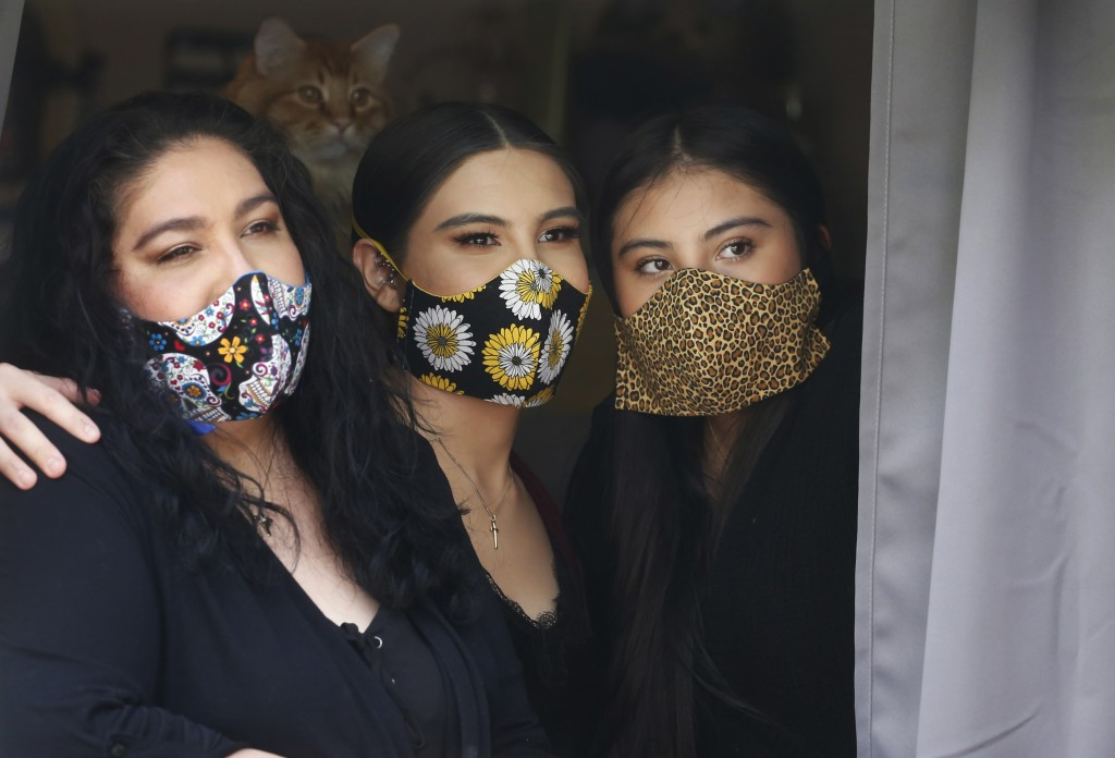 In this Monday, May 18, 2020, photo, Anissa Archuleta, center, sits at a window with her sister Alexis Archuleta, right, and her mother, Jaime Ortega,...