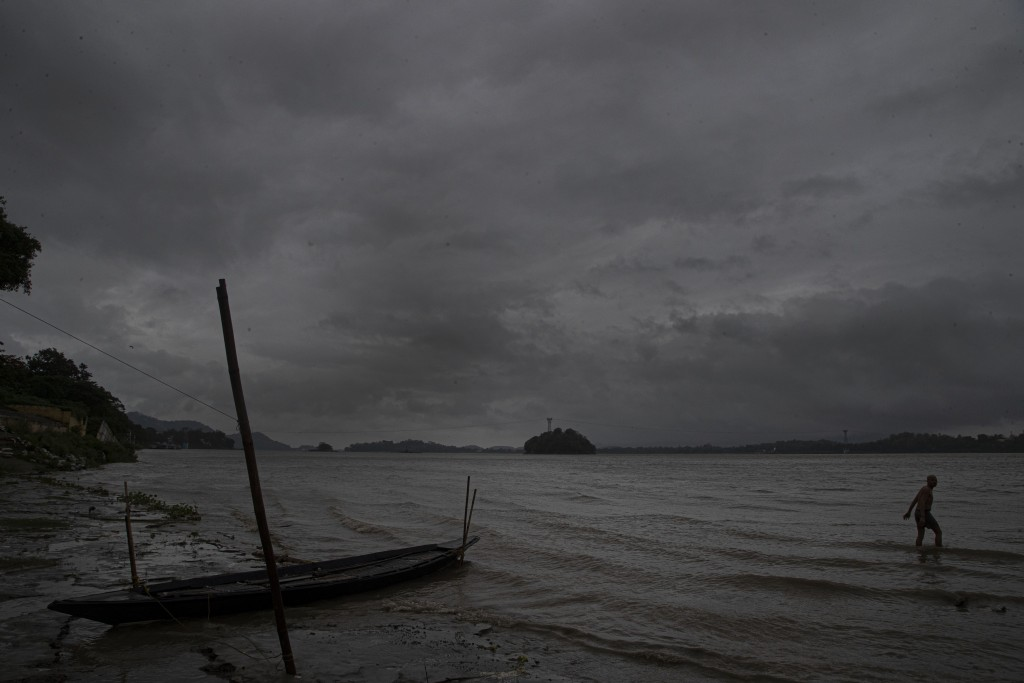 An Indian fisherman walks in the middle of heavy wind and rain in the river Brahmaputra in Gauhati, India, Thursday, May 21, 2020. A powerful cyclone ...