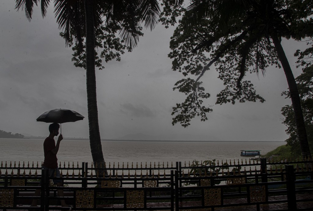 An Indian man walks with his umbrella in the middle of heavy wind and rain along the river Brahmaputra in Gauhati, India, Thursday, May 21, 2020. A po...