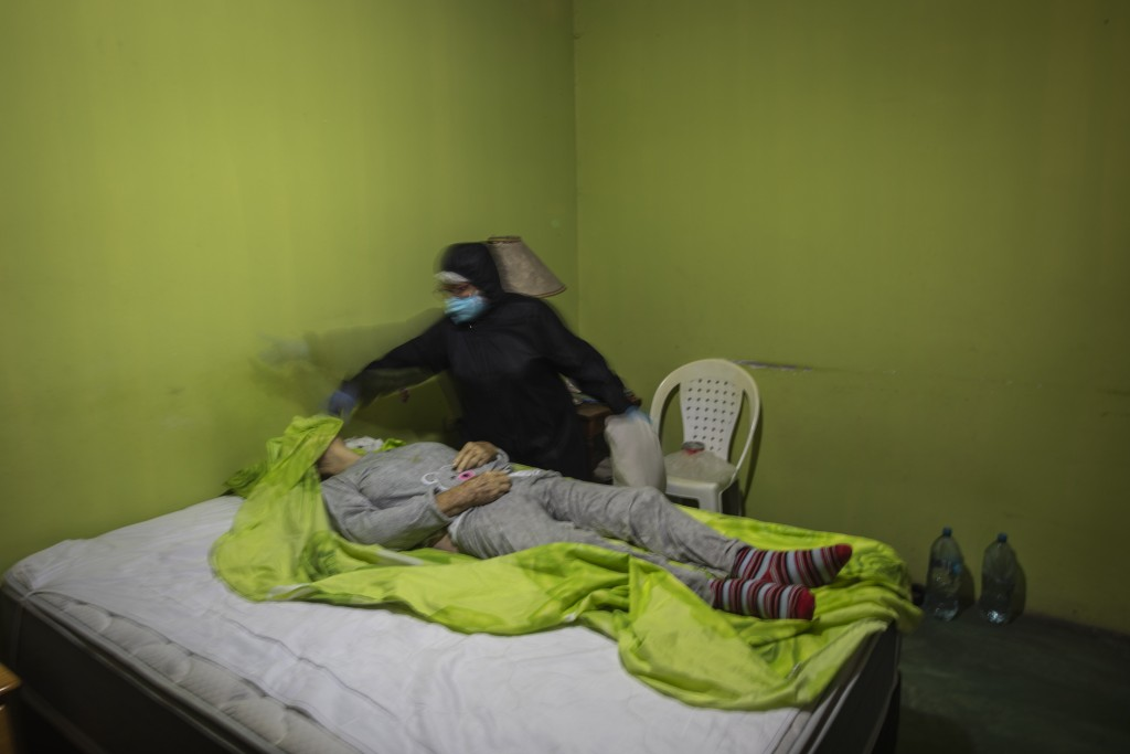 A woman covers with a bed sheet the face of her deceased mother-in-law suspected of dying from the new coronavirus, in Lima, Peru, Thursday, May 14, 2...