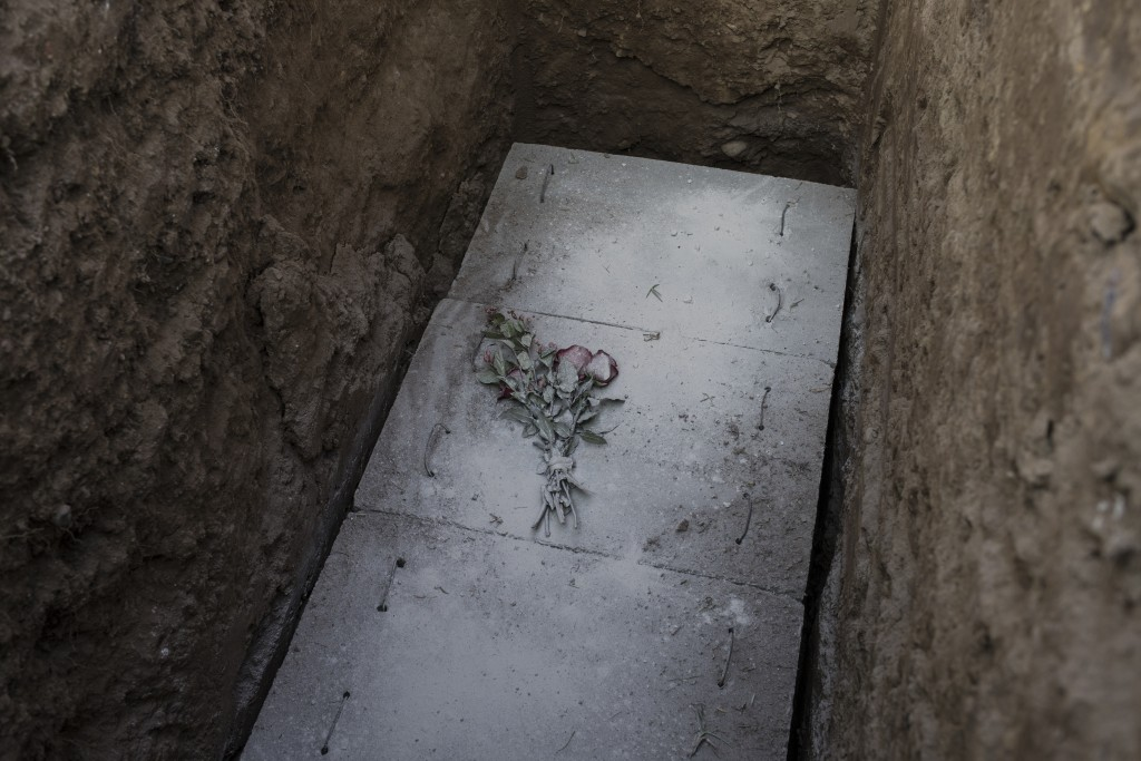 Red roses dusted with lime cement lay on a concrete slab covering the coffin containing the remains of cameraman Mario Bucana who is suspected to have...