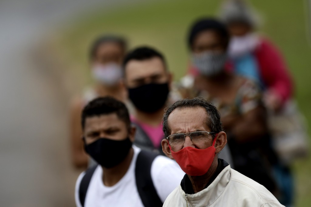People wear masks against the spread of the new coronavirus, at a bus stop in Valparaiso, Brazil, Wednesday, May 20, 2020. Valparaiso, 40 km. (about 2...