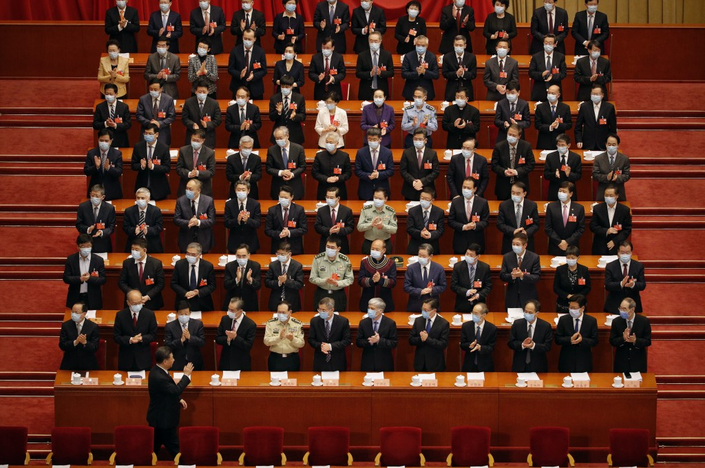 Chinese President Xi Jinping, at bottom, gestures as he arrives for the opening session of the Chinese People's Political Consultative Conference (CPP...