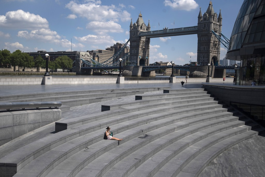 A woman sits in 'More London', during what would normally be the busy lunch period, amid the coronavirus outbreak, in London, Thursday May 21, 2020. (...