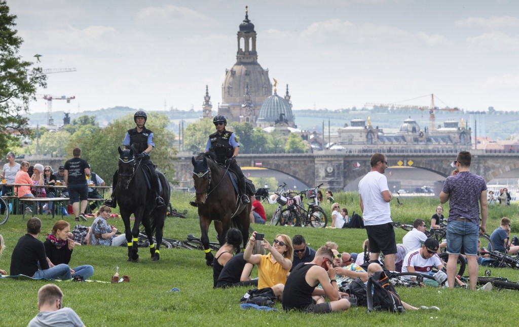 Two police officers on horses patrol between visitors of a beer garden in Dresden, Germany, Thursday, May 21, 2020. Due to the new coronavirus outbrea...