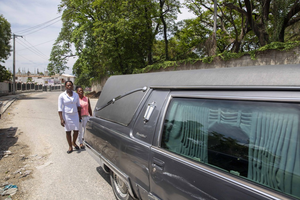 Ermilia Luberice, left, mourns with her friend Yolande Jean Louis, as they accompany the hearse with the body of her 7-year-old daughter Lovena Luberi...
