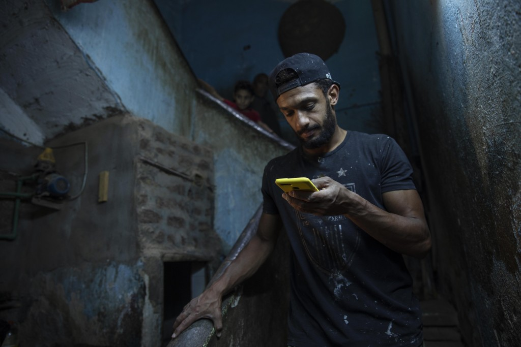 28-year-old football defender Mahrous Mahmoud, stops to look at his phone as he walks down the stairs of the building where he lives, in Manfalut, a t...
