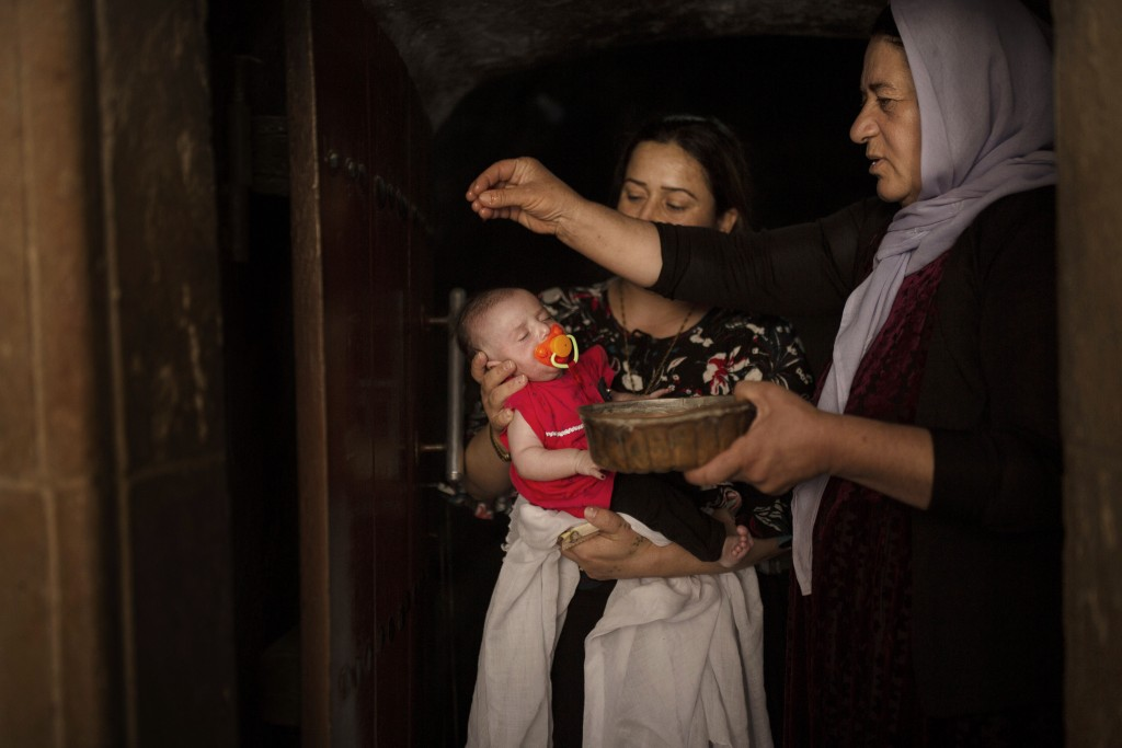 In this Aug. 23, 2019 photo, a baby girl is annointed with water from an ancient spring by a Yazidi holy woman at the the Lalish temple near Sheikhan,...