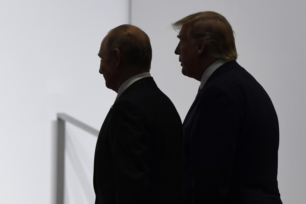 FILE - In this June 28, 2019, file photo, President Donald Trump and Russian President Vladimir Putin walk to participate in a group photo at the G20 ...
