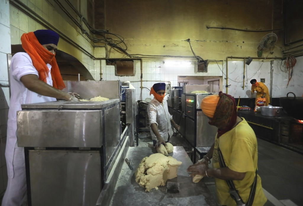 Sikh volunteers put dough into a machine that makes chapati, thin unleavened bread, in the kitchen hall of the Bangla Sahib Gurdwara in New Delhi, Ind...